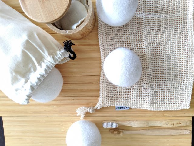 Naturally colored home goods (wool dryer balls, cotton makeup rounds, cotton mesh produce bag, and bamboo toothbrush) on a bamboo background are sample of the products and aesthetic we sell.